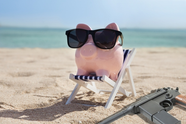 PiggyBank on Beach with gun_shutterstock_266589911